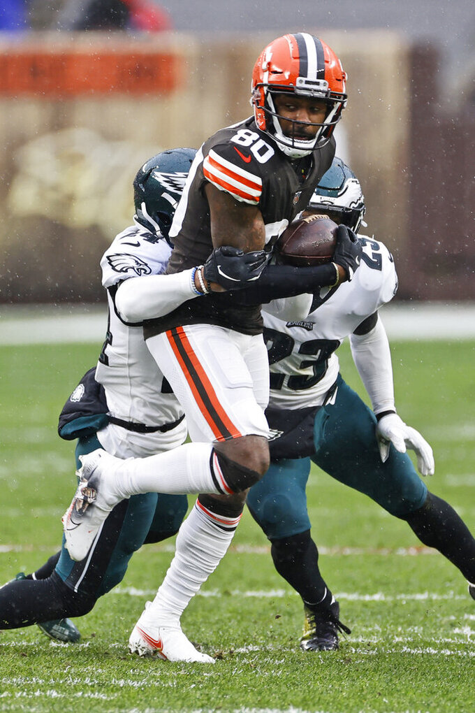 Cleveland Browns wide receiver Jarvis Landry (80) is tackled by Philadelphia Eagles cornerback Darius Slay (24) and free safety Rodney McLeod (23) during the first half of an NFL football game, Sunday, Nov. 22, 2020, in Cleveland. (AP Photo/Ron Schwane)