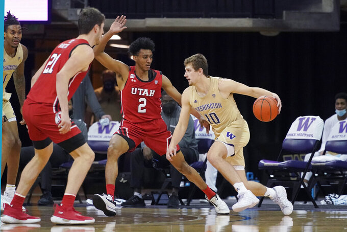 Washington guard Erik Stevenson drives past Utah guard Ian Martinez (2) during the second half of an NCAA college basketball game, Sunday, Jan. 24, 2021, in Seattle. Washington won 83-79. (AP Photo/Ted S. Warren)
