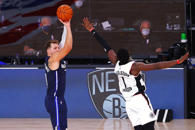 Dallas Mavericks' Luka Doncic, left, hits a winning three-point basket against Los Angeles Clippers' Reggie Jackson (1) during overtime of Game 4 of an NBA basketball first-round playoff series, Sunday, Aug. 23, 2020, in Lake Buena Vista, Fla. (Kevin C. Cox/Pool Photo via AP)
