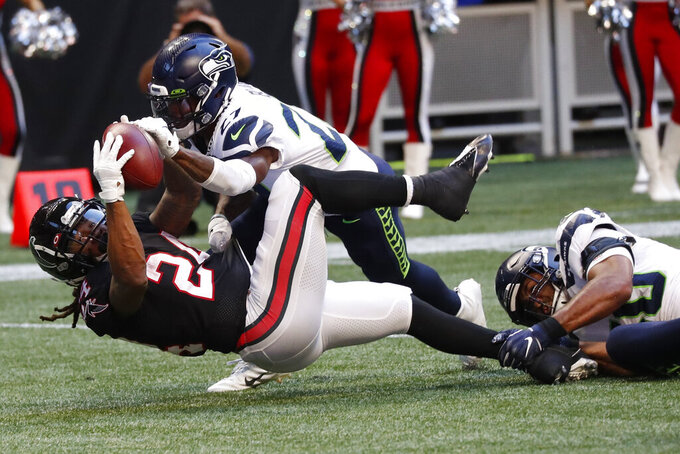 Seattle Seahawks defensive back Marquise Blair (27) strips the ball from Atlanta Falcons running back Devonta Freeman (24) during the second half of an NFL football game, Sunday, Oct. 27, 2019, in Atlanta. Seattle Seahawks recovered on the play. (AP Photo/John Bazemore)