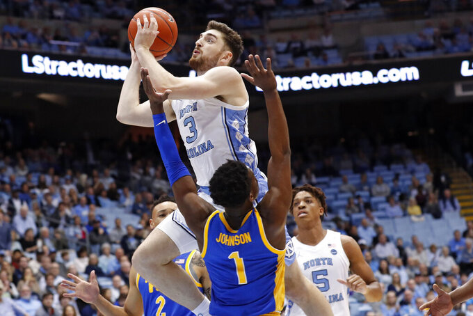 North Carolina guard Andrew Platek (3) shoots over Pittsburgh guard Xavier Johnson (1) during the first half of an NCAA college basketball game in Chapel Hill, N.C., Wednesday, Jan. 8, 2020. (AP Photo/Gerry Broome)