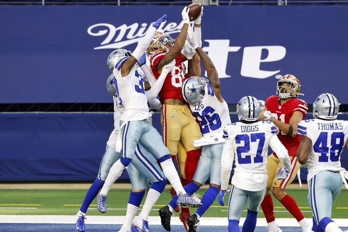 San Francisco 49ers wide receiver Kendrick Bourne (84) leaps above Dallas Cowboys' Donovan Wilson, left, and Jourdan Lewis (26) to catch a Hail Mary pass in the end zone for a touchdown in the second half of an NFL football game in Arlington, Texas, Sunday, Dec. 20, 2020. (AP Photo/Michael Ainsworth)