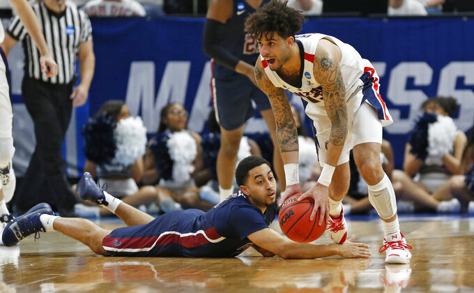 Gonzaga guard Josh Perkins battles Fairleigh Dickinson guard Tyler Jones, bottom, for a loose ball during the second half of a first-round game in the NCAA men's college basketball tournament Thursday, March 21, 2019, in Salt Lake City. (AP Photo/Rick Bowmer)