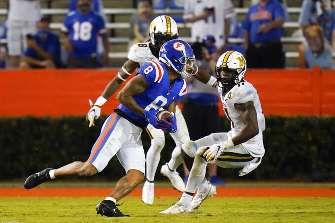 Florida wide receiver Trevon Grimes, center, runs past Missouri defensive back Jarvis Ware, left, and linebacker Devin Nicholson, right, for an 18-yard touchdown on a pass play during the second half of an NCAA college football game, Saturday, Oct. 31, 2020, in Gainesville, Fla. (AP Photo/John Raoux)