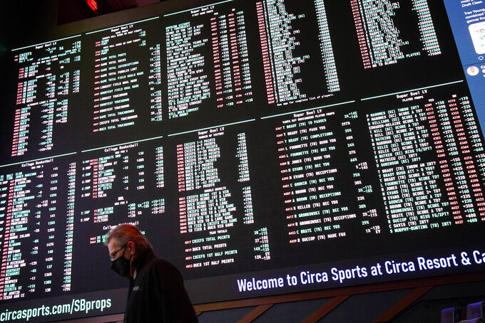 FILE- In this Feb. 3, 2021, file photo, a man walks by as betting odds for NFL football's Super Bowl 55 are displayed on monitors at the Circa resort and casino sports book in Las Vegas. Three years after the Supreme Court overturned the Professional and Amateur Sports Protection Act and allowed states to legalize sports betting, the NFL has embraced gambling as part of the landscape. (AP Photo/John Locher, File)