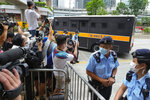 Police officers stand guard as a prison truck carrying Tong Ying-kit leaves a court Friday, July 30, 2021, after his sentencing for the violation of a security law during a 2020 protest. Tong has been sentenced to nine years in prison in the closely watched first case under Hong Kong's national security law as Beijing tightens control over the territory. (AP Photo Vincent Yu)