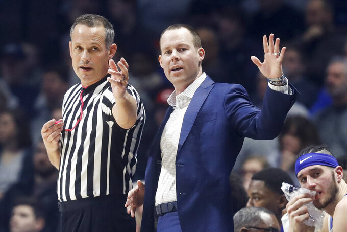 Xavier head coach Travis Steele, right, speaks with a referee during the first half of an NCAA college basketball game against Marquette, Saturday, Jan. 26, 2019, in Cincinnati. (AP Photo/John Minchillo)