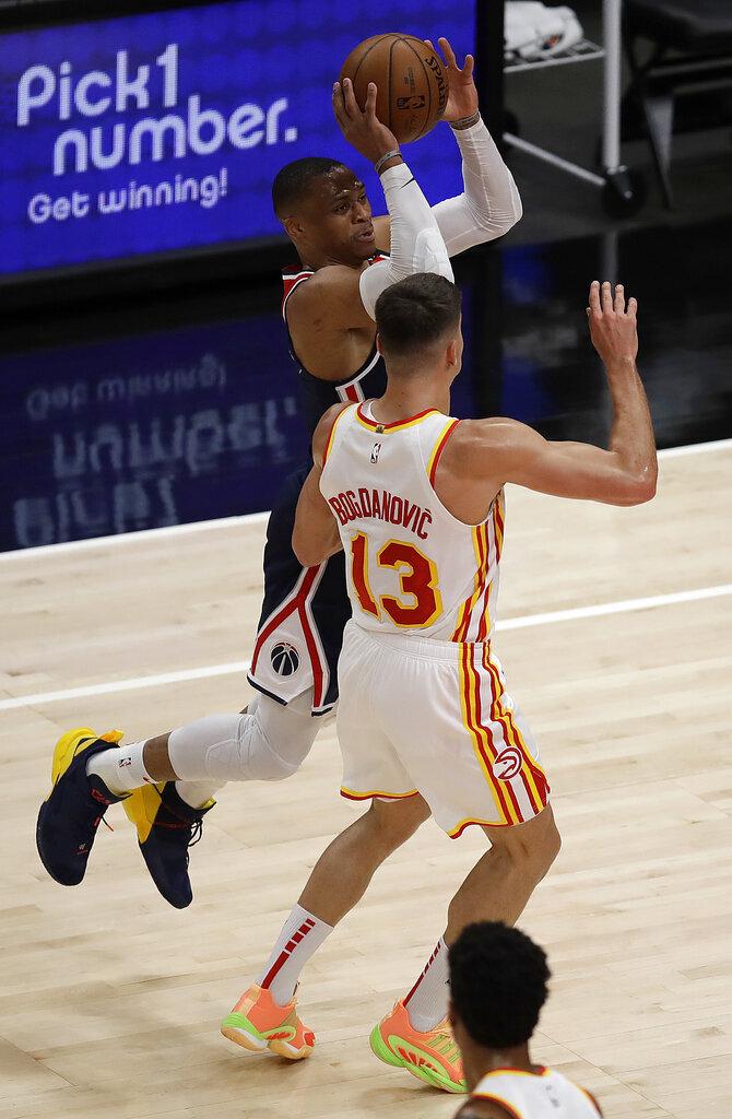 Washington Wizards' Russell Westbrook, left, shoots over Atlanta Hawks' Bogdan Bogdanovic, right, during the first half of an NBA basketball game Monday, May 10, 2021, in Atlanta. (AP Photo/Ben Margot)