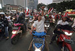 Supporters of Indonesian President Joko Widodo celebrate during a rally in Jakarta, Indonesia, Wednesday, April 17, 2019. Widodo is on track to win a second term, preliminary election results showed Wednesday, in apparent victory for moderation over the ultra-nationalistic rhetoric of his rival Prabowo Subianto. (AP Photo/Dita Alangkara)