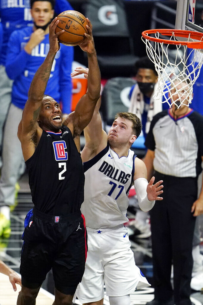 Los Angeles Clippers forward Kawhi Leonard (2) dunks against Dallas Mavericks guard Luka Doncic (77) during the second half in Game 2 of an NBA basketball first-round playoff series Tuesday, May 25, 2021, in Los Angeles. (AP Photo/Marcio Jose Sanchez)