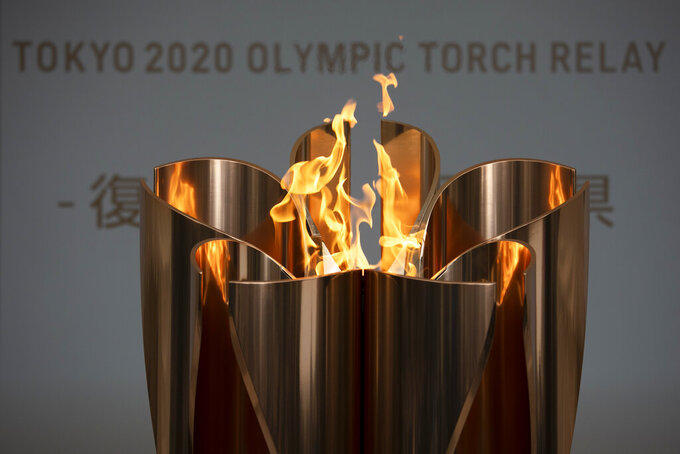 """FILE - In this March 24, 2020, file photo, the Olympic Flame burns during a ceremony in Fukushima City, Japan. The Olympic flame is going to be on display until the end of April in Japan's northeastern prefecture of Fukushima. Tokyo Olympic and prefecture officials held an official """"handover ceremony""""on Wednesday, April 1, at the J-Village National Training Center in Fukushima.(AP Photo/Jae C. Hong, File)"""