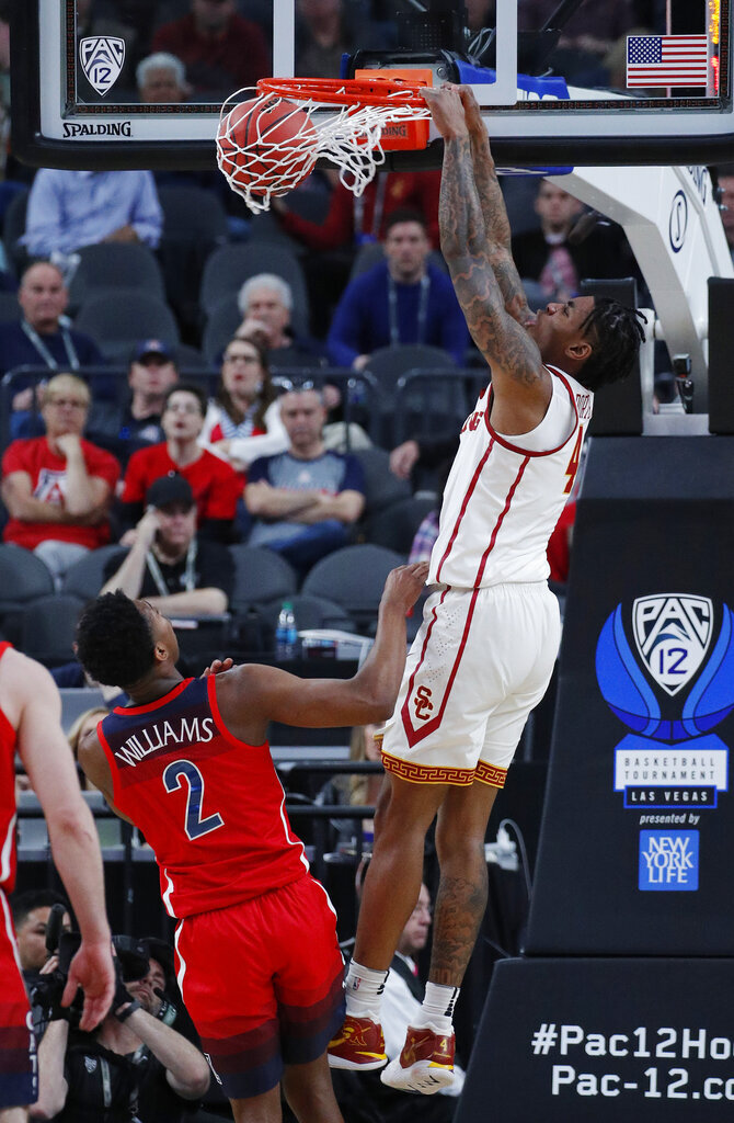 Southern California's Kevin Porter Jr. dunks over Arizona's Brandon Williams during the second half of an NCAA college basketball game in the first round of the Pac-12 men's tournament Wednesday, March 13, 2019, in Las Vegas. (AP Photo/John Locher)