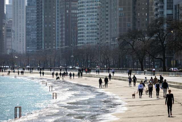 Residents enjoy the warm weather with a stroll along the Lakefront Trail near Oak Street Beach, Wednesday afternoon, March 25, 2020, in Chicago, despite a stay-at-home order from Illinois Gov. J.B. Pritzker during the coronavirus pandemic. The new coronavirus causes mild or moderate symptoms for most people, but for some, especially older adults and people with existing health problems, it can cause more severe illness or death.  (Ashlee Rezin Garcia/Chicago Sun-Times via AP)