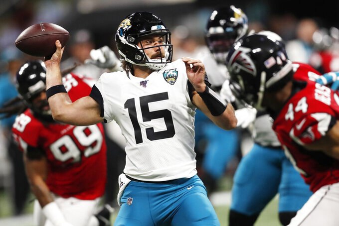 FILE - In this Dec. 22, 2019, file photo, Jacksonville Jaguars quarterback Gardner Minshew II (15) works in the pocket against the Atlanta Falcons during the first half of an NFL football game in Atlanta. Minshew could end up being Jacksonville's best late-round draft pick. The sixth-round selection from Washington State threw 21 touchdown passes and six interceptions in 12 starts as a rookie last season. He also directed three fourth-quarter comebacks. (AP Photo/John Bazemore, File)