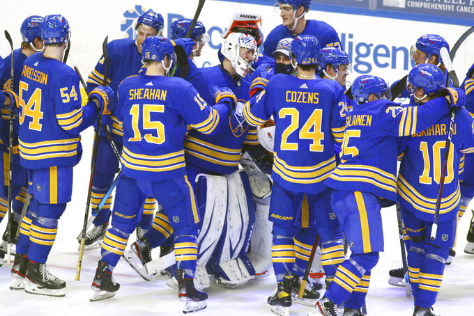 FILE - In this May 4, 2021, file photo, Buffalo Sabres goalie Michael Houser (32) and teammates celebrate a victory over the New York Islanders in a shootout in an NHL hockey game in Buffalo, N.Y. The Sabres won the NHL draft lottery and the expansion Seattle Kraken jumped up the order to take the No. 2 pick Wednesday night, June 2. (AP Photo/Jeffrey T. Barnes, File)