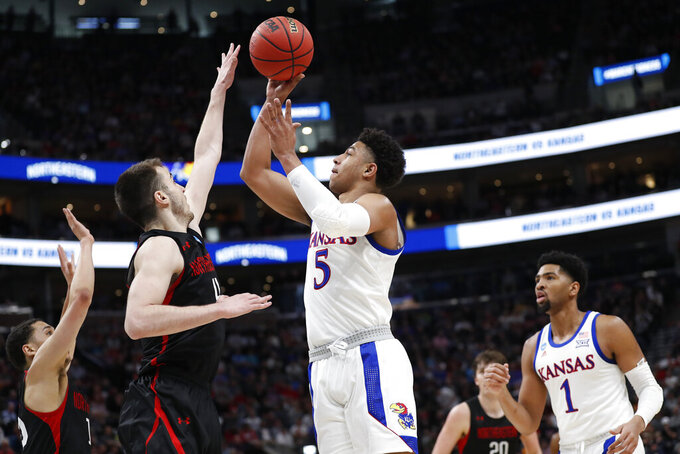 Northeastern guard Vasa Pusica, left blocks a shot by Kansas guard Quentin Grimes (5) in the first half during a first round men's college basketball game in the NCAA Tournament Thursday, March 21, 2019, in Salt Lake City. (AP Photo/Jeff Swinger)