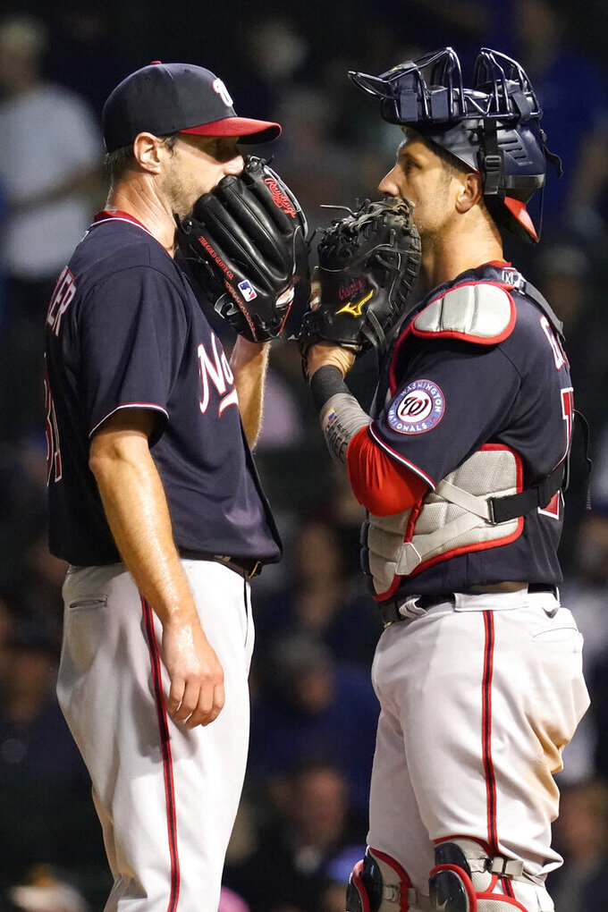 Washington Nationals starting pitcher Max Scherzer, left, talks with catcher Yan Gomes during the fifth inning of a baseball game against the Chicago Cubs in Chicago, Wednesday, May 19, 2021. (AP Photo/Nam Y. Huh)