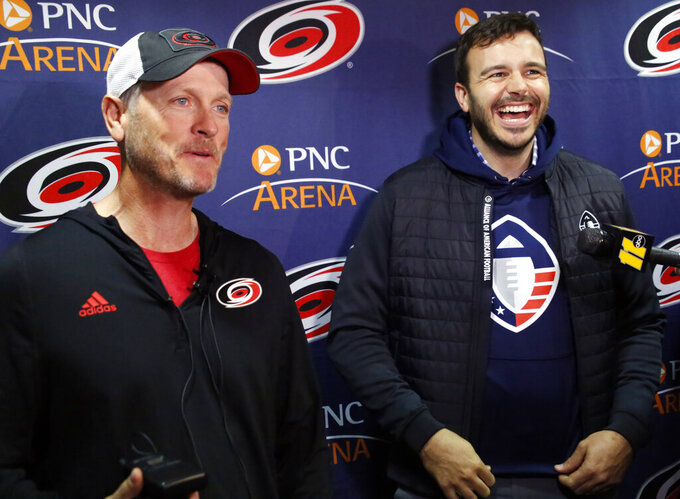 FILE - In this Feb. 19, 2019, file photo, Tom Dundon, left, majority owner of the Carolina Hurricanes, and Charlie Ebersol, co-founder and CEO of the Alliance of American Football, talk to the media in Raleigh, N.C. The Alliance of American Football is suspending operations eight games into its first season. A person with knowledge of the decision tells The Associated Press the eight-team spring football league is not folding, but games will not be played this weekend. The decision was made by majority owner Tom Dundon. The person spoke to The Associated Press on condition of anonymity because league officials were still working through details of the suspension. An announcement from the league is expected later Tuesday, April 2, 2019. (AP Photo/Chris Seward, File)