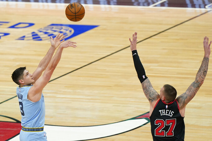 Memphis Grizzlies guard Grayson Allen, left, shoots against Chicago Bulls center Daniel Theis during the first half of an NBA basketball game in Chicago, Friday, April 16, 2021. (AP Photo/Nam Y. Huh)
