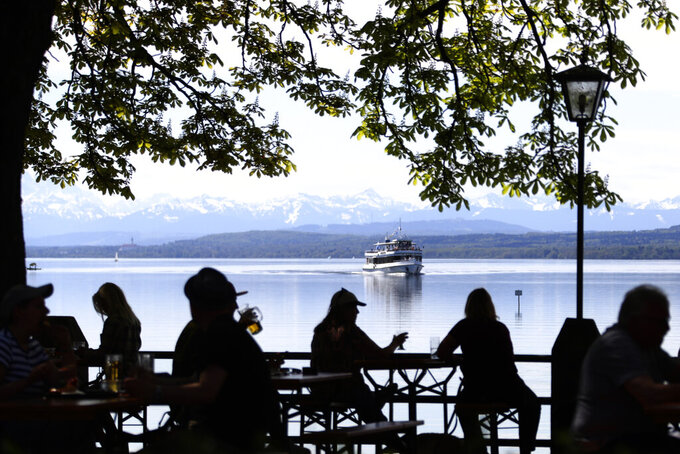 FOR HOLD - In this Monday, May 10, 2021 file photo, people enjoy the sunny weather and drink beer on the re-opening day of beer gardens, following the lifting of measures to avoid the spread of the corona virus, at Bavarian lake 'Ammersee' in front of the alps in Inning, Germany. Germany has overall managed the pandemic far better than many of its peers and its daily death toll remains significantly below that of neighboring France, which has a smaller population, for instance. All three candidates for chancellor have said no further lockdown is planned. (AP Photo/Matthias Schrader, File)