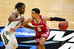 Wisconsin guard D'Mitrik Trice (0) drives on Baylor guard Davion Mitchell (45) in the first half of a second-round game in the NCAA men's college basketball tournament at Hinkle Fieldhouse in Indianapolis, Sunday, March 21, 2021. (AP Photo/Michael Conroy)