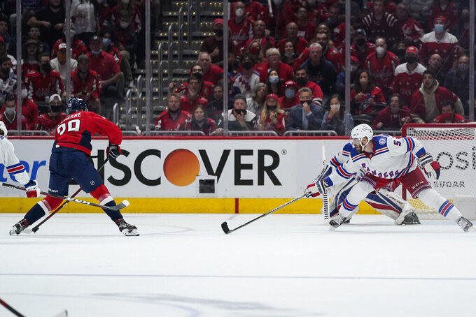 Washington Capitals center Hendrix Lapierre (29) prepares to shoot, scoring a goal, as New York Rangers' Jarred Tinordi (5) defends during the second period of an NHL hockey game Wednesday, Oct. 13, 2021, in Washington. (AP Photo/Alex Brandon)