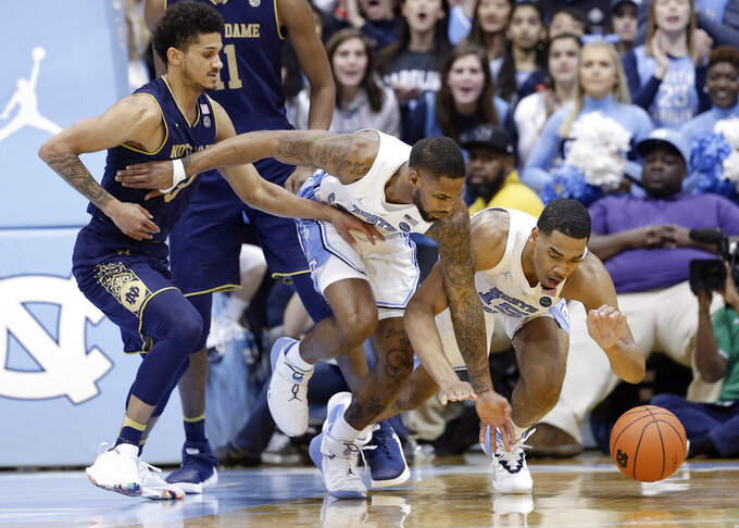 Notre Dame's Prentiss Hubb, left, reaches for a loose ball with North Carolina's Seventh Woods and Garrison Brooks, right, during the first half of an NCAA college basketball game in Chapel Hill, N.C., Tuesday, Jan. 15, 2019. (AP Photo/Gerry Broome)