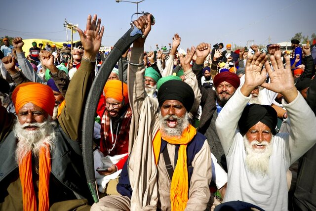 Protesting farmer leaders shout slogans as they sit on a day long hunger strike at the Delhi- Haryana border, outskirts of New Delhi, Monday, Dec.14, 2020. Tens of thousands of protesting Indian farmers have called for a national strike on Monday, the second in a week, to press for the quashing of three new laws on agricultural reform that they say will drive down crop prices and devastate their earnings. (AP Photo/Manish Swarup)