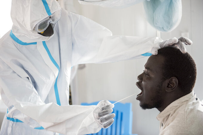 In this photo taken Sunday, June 21, 2020, an infectious disease specialist, left, takes a sample from Dr. Reagan Taban Augustino, right, now a coronavirus patient himself under quarantine, at the Dr John Garang Infectious Diseases Unit in Juba, South Sudan. The United Nations says the country's outbreak is growing rapidly, with nearly 1,900 cases, including more than 50 health workers infected, and at the only laboratory in the country that tests for the virus a team of 16 works up to 16-hour days slogging through a backlog of more than 5,000 tests. (AP Photo/Charles Atiki Lomodong)