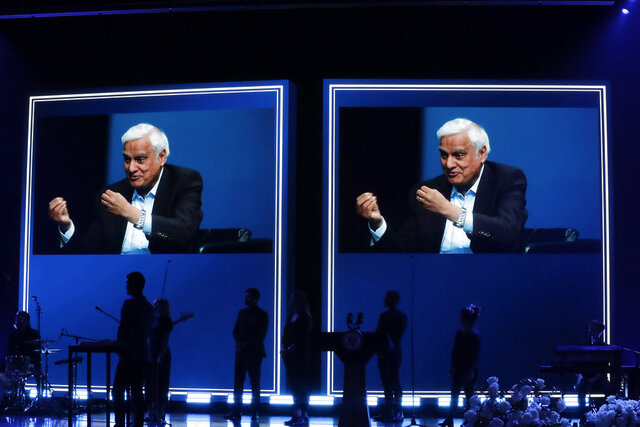 FILE - In this May 29, 2020 file photo, images of Ravi Zacharias are displayed in the Passion City Church during a memorial service for him in Atlanta. A posthumous sex scandal involving  Zacharias, who founded the Ravi Zacharias International Ministries has placed the global organization in a wrenching predicament. (AP Photo/Brynn Anderson, File)
