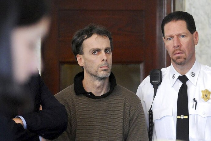 In this Jan. 29, 2009, photo, Sean Murphy, alleged mastermind behind a $2 million jewelry heist from the E.A. Dion jewelry manufacturing company in 2008, in Attleboro, Mass., listens to a list of charges brought against him during arraignment in Attleboro District Court. At right is court officer Howie Werman. In a February 2020 letter to The Associated Press, the career criminal said he is hoping to catch a break on his prison sentence from burglarizing a Brink's warehouse in Columbus, Ohio, during which he accidentally set millions of dollars on fire. (Mark Stockwell/The Sun Chronicle via AP)