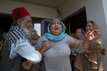 Relatives comfort the wife of civilian Bashir Ahmed Khan at their residence on the outskirts of Srinagar, Indian controlled Kashmir, Wednesday, July 1, 2020. Suspected rebels attacked paramilitary soldiers in the Indian portion of Kashmir, killing Khan and a paramilitary soldier, according to government sources. The family refutes the claim. (AP Photo/ Dar Yasin)