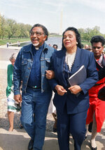 FILE - In this April 21, 1988, file photo, Coretta Scott King, widow of the Rev. Dr. Martin Luther King Jr., and the Rev. Joseph E. Lowery, president of the Southern Christian Leadership Conference, walk arm in arm after announcing plans for a rally during a news conference at the Lincoln Memorial in Washington. Lowery, a veteran civil rights leader who helped King Jr. found the SCLC and fought against racial discrimination, died Friday, March 27, 2020, a family statement said. He was 98. (AP Photo/Bob Daugherty, File)