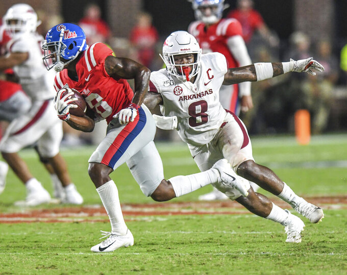 Mississippi wide receiver Elijah Moore (8) escapes Arkansas linebacker De'Jon Harris (8) to score during an NCAA college football game Saturday, Sept. 7, 2019, in Oxford, Miss. (Bruce Newman/The Oxford Eagle via AP)