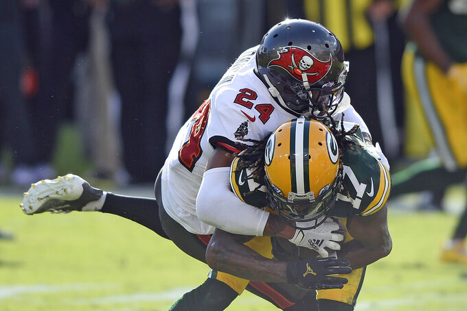 Tampa Bay Buccaneers cornerback Carlton Davis (24) takes down Green Bay Packers wide receiver Davante Adams (17) after a catch during the first half of an NFL football game Sunday, Oct. 18, 2020, in Tampa, Fla. (AP Photo/Jason Behnken)