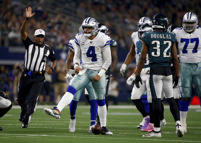 Dallas Cowboys quarterback Dak Prescott (4) celebrates after running the ball as Philadelphia Eagles' Rasul Douglas (32) looks on in the first half of an NFL football game in Arlington, Texas, Oct. 20, 2019. (AP Photo/Ron Jenkins)
