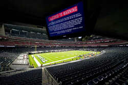 A COVID-19 warning is displayed as the Houston Texans and the Baltimore Ravens play an NFL football game with out fans present, Sunday, Sept. 20, 2020, in Houston. (AP Photo/Eric Gay)