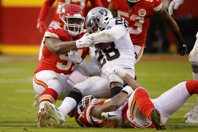 Kansas City Chiefs linebacker Damien Wilson (54) and defensive tackle Derrick Nnadi, bottom, tackle Oakland Raiders running back Josh Jacobs (28) during the first half of an NFL football game in Kansas City, Mo., Sunday, Dec. 1, 2019. (AP Photo/Charlie Riedel)
