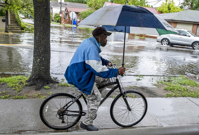 A man rides a bicycle while holding an umbrella as rain from Tropical Storm Bertha flooded a few streets in Charleston, S.C., Wednesday, May 27, 2020. (Matthew Fortner/The Post And Courier via AP)