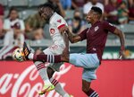 Toronto FC midfielder Richie Laryea (22) leaps for the ball against Colorado Rapids midfielder Mark-Anthony Kaye in the first half of an MLS soccer game in Denver, Saturday, Sept. 25, 2021. (AP Photo/Joe Mahoney)