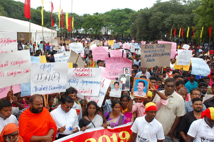 Sri Lankan ethnic Tamils hold placards during a public rally in northern Jaffna, Sri Lanka, Monday, Sept. 16, 2019. Shops have shut in Sri Lanka's ethnic Tamil-majority north in support of a rally demanding an international probe into alleged atrocities committed during the nation's civil war and an end to alleged state-sponsored efforts to change the ethnic demography of the Tamils' traditional homeland. (AP Photo/ Mariyathas Newton)