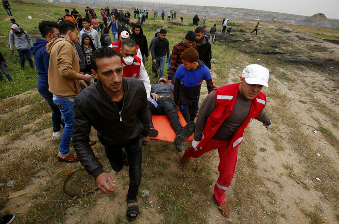 Medics and protester evacuate a wounded youth, who was shot by Israeli troops from near the fence of the Gaza Strip's border with Israel, while marking first anniversary of Gaza border protests east of Gaza City, Saturday, March 30, 2019. Tens of thousands of Palestinians on Saturday gathered at rallying points near the Israeli border to mark the first anniversary of weekly protests in the Gaza Strip, as Israeli troops fired tear gas and opened fire at small crowds of activists who approached the border fence. (AP Photo/Abdel kareem Hana)