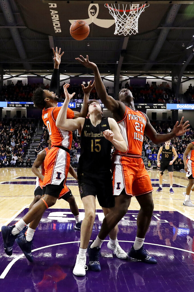 Illinois guard Alan Griffin, left, and center Kofi Cockburn, right, reach for a rebound over Northwestern center Ryan Young during the first half of an NCAA college basketball game in Evanston, Ill., Thursday, Feb. 27, 2020. (AP Photo/Nam Y. Huh)