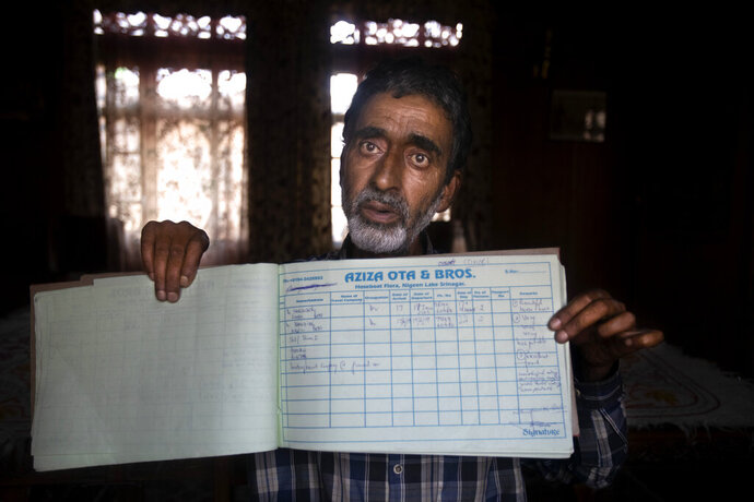 A Kashmiri houseboat owner Ghulam Qadir shows his guest entry book which was last filled in July 2019, in Srinagar, Indian controlled Kashmir,Tuesday, July 28, 2020. Indian-controlled Kashmir's economy is yet to recover from a colossal loss a year after New Delhi scrapped the disputed region's autonomous status and divided it into two federally governed territories. (AP Photo/Mukhtar Khan)