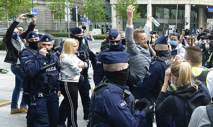 Police, wearing face masks to protect against coronavirus, detain independent candidate in Poland's presidential election, Pawel Tanajno, center, during a small protest of business people opposing coronavirus lockdown measures, in Warsaw, Poland, Saturday, May 23, 2020. (AP Photo/Czarek Sokolowski)