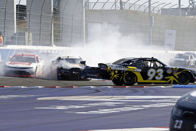 Josh Bilicki (93) spins in front of JJ Yeley and Michael Annett, left, in Turn 11 during the the NASCAR Xfinity Series auto race at Charlotte Motor Speedway in Concord, N.C., Saturday, Sept. 28, 2019. (AP Photo/Wesley Broome)