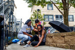 Jalisa Ford sits on the ground while rubbing the walkway where her 9-year-old son Janari Ricks was fatally shot while playing with friends at the Cabrini Green townhomes Saturday Aug. 1, 2020 in Chicago. A suspect has been arrested in the fatal shooting of the 9-year-old boy and police hope to secure charges against him in the coming days, the city's police superintendent said Monday, Aug. 3, 2020. (Armando L. Sanchez/Chicago Tribune via AP)