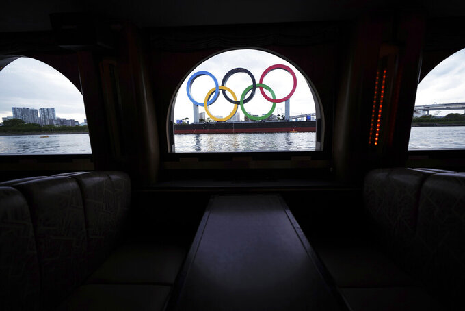 """The Olympic rings floating in the water in the Odaiba section are seen from a window of a water bus Monday, April 12, 2021, in Tokyo. Tokyo pitched itself as """"a safe pair of hands"""" when it was awarded the Olympics 7 1/2 years ago. Now, nothing is certain as Tokyo's postponed Olympics hit the 100-days-to-go mark on Wednesday, April 14, 2021. (AP Photo/Eugene Hoshiko)"""