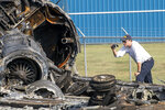 A member of the National Transportation Safety Board looks at the wreckage of a plane that Dale Earnhardt Jr., his wife and daughter and two pilots and a dog were on when it crash landed Thursday at the Elizabethton Municipal Airport in Elizabethton, Tenn., Friday, Aug. 16, 2019. Earnhardt Jr. will take the weekend off from broadcasting to be with his wife and daughter after the crash near Bristol Motor Speedway. (David Crigger/Bristol Herald Courier via AP)