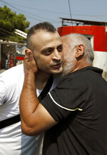 Australian-Lebanese dual citizen Amer Khayyat, left, kisses his brother Fadi, after his release from prison in Roumieh, east of Beirut, Lebanon, Friday, Sept. 20, 2019. Lebanese authorities have released the Lebanese-Australian who had been detained in Lebanon for more than two years after he was found innocent in an alleged plot to bring down a passenger plane bound for the United Arab Emirates from Sydney. (AP Photo/Bilal Hussein)